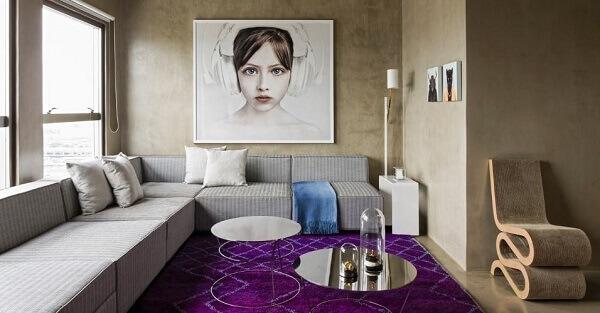 O tapete roxo quebra a neutralidade do sofá de canto cinza claro