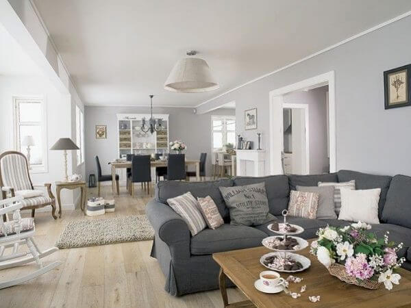 O vaso de flor alegra a decoração da sala com sofá de canto cinza