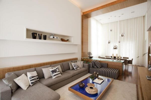 Para uma decoração clean combine o sofá de canto cinza claro com parede branco