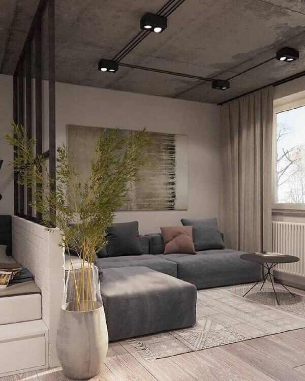 Para uma decoração industrial combine trilhos eletrificados com um lindo sofá de canto cinza