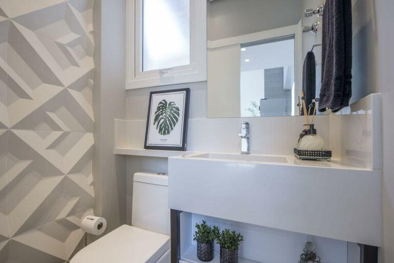 Parede com revestimento 3D para banheiro e cuba esculpida branca