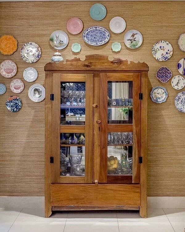 Pratos decorativos decoram a parede acima da cristaleira de madeira