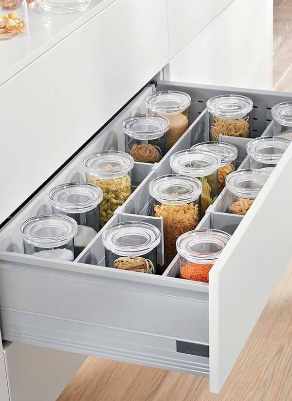 Utilize potes de vidro para organizar os mantimentos dentro da gaveta da despensa de cozinha