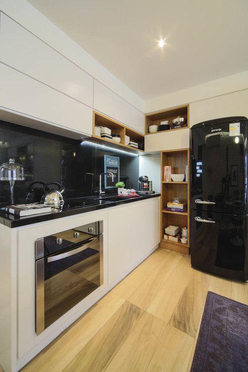 Cozinha modulada de canto com armários brancos e geladeira preta