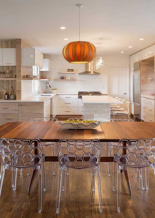 cadeira de plástico transparente para sala de jantar com mesa de madeira integrada com cozinha planejada Foto Constance Zahn