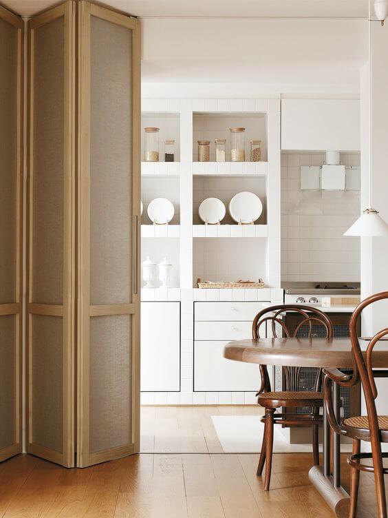 Cozinha com porta sanfonada e móveis de madeira