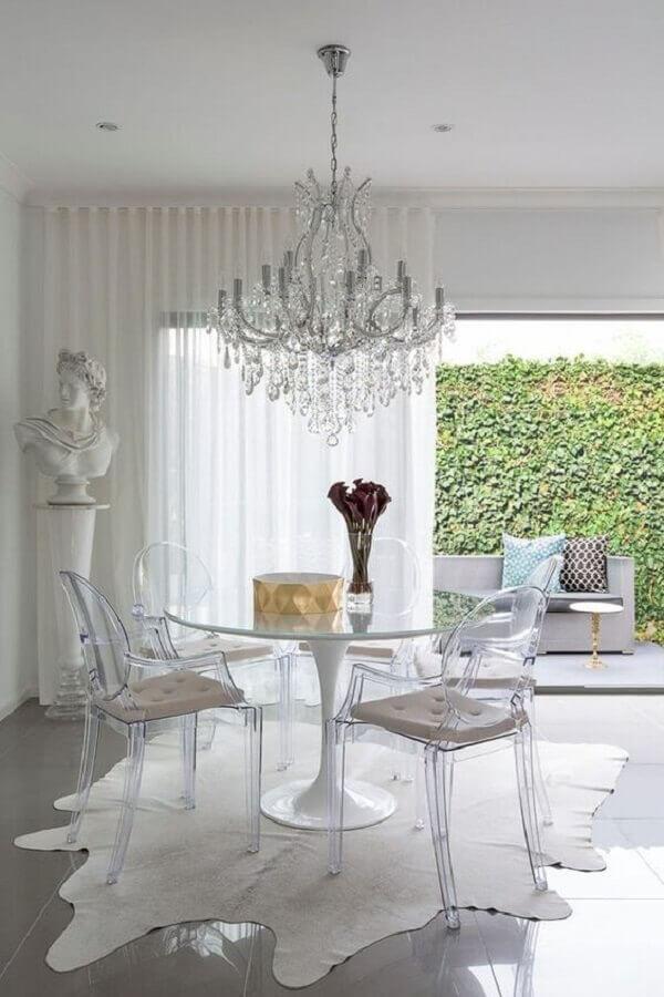 decoração clean para sala de jantar com lustre de cristal e cadeira transparente com braço Foto Apartment Therapy