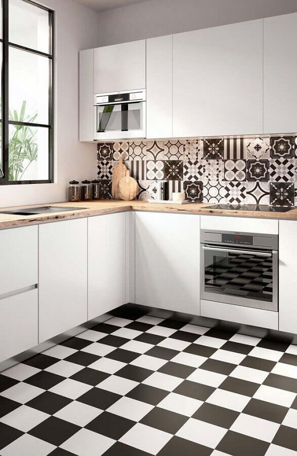 decoração com revestimento preto e branco e armário branco de cozinha de canto com bancada de madeira Foto Apartment Therapy