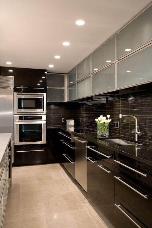 decoração para cozinha escura com armário preto planejado e armário aéreo com portas de vidro Foto Futurist Architecture