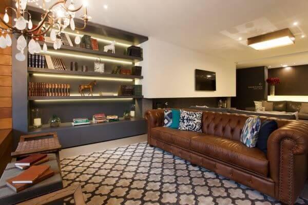 Sala de estar com sofá chesterfield com almofada estampada