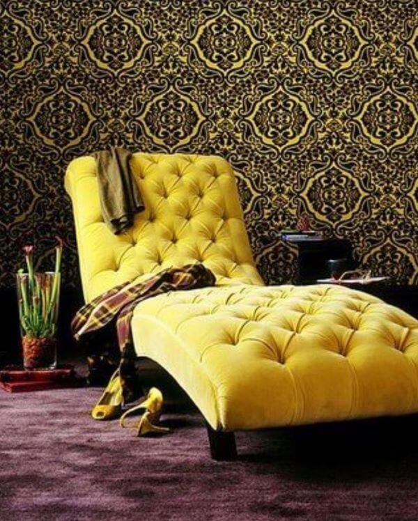 Divã amarelo no quarto com papel de parede