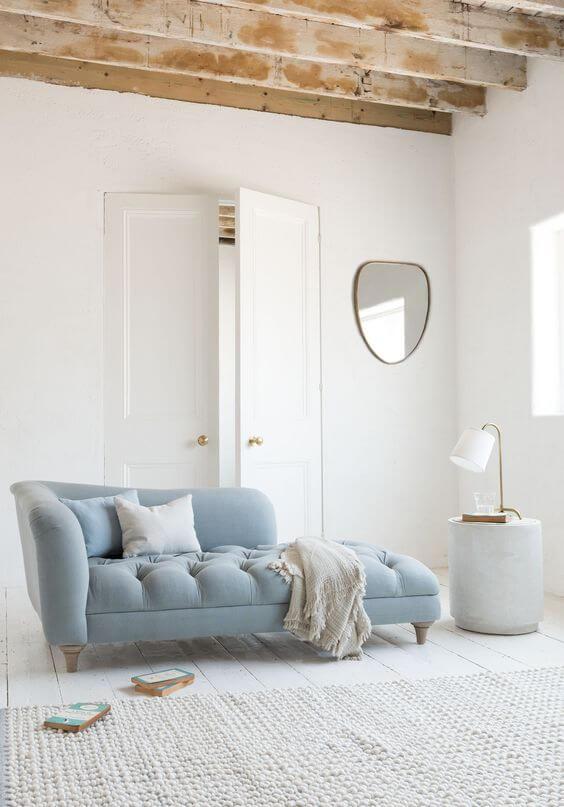 Sofá divã azul claro com manta neutra