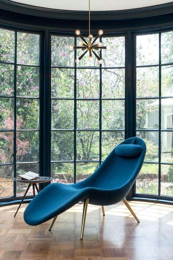Divã azul moderno no cantinho da leitura iluminado