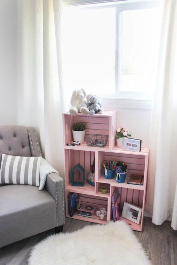 Estante de pallete cor de rosa no quarto infantil
