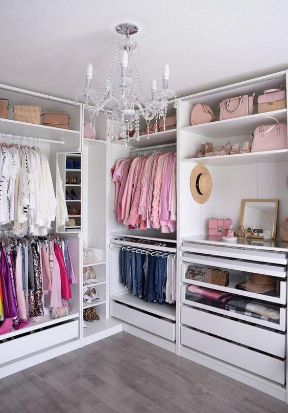 Guarda roupa de canto no closet moderno com lustre luxuoso