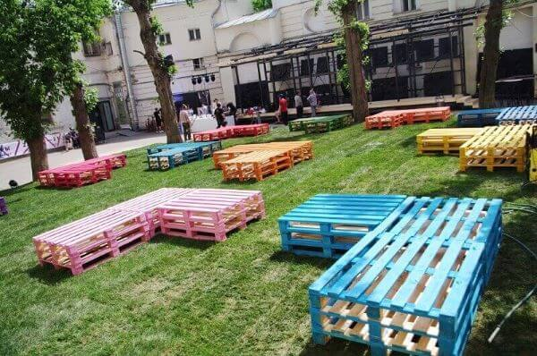 Jardim com bancos de pallets coloridos