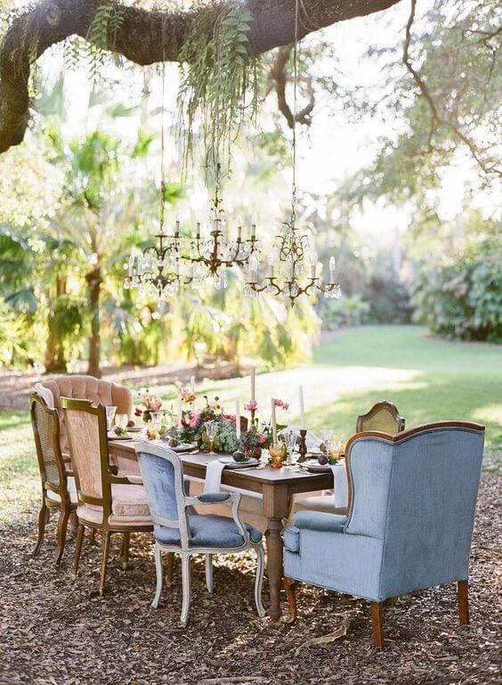 Mesa de jantar para festa boho chic com poltronas e cadeiras diferentes