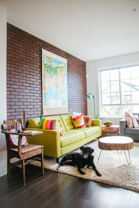 Papel de parede tijolinho a vista com sofá amarelo em destaque