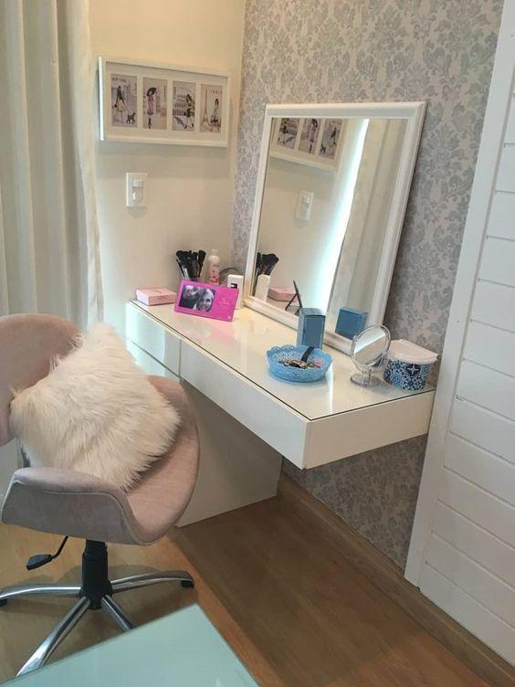 Penteadeira suspensa com poltrona rosa e almofada branca