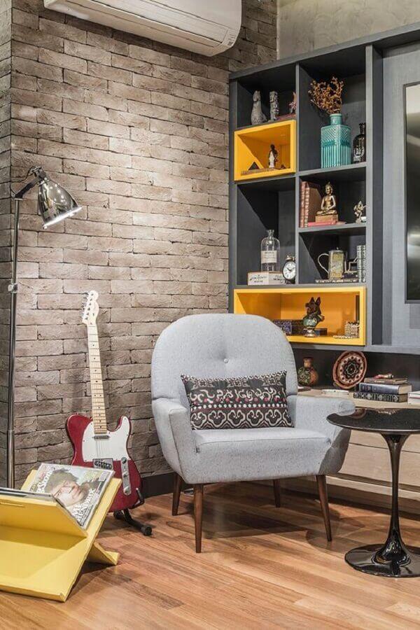 poltrona decorativa cinza para sala com parede de tijolinho e guitarra Foto Casa de Valentina