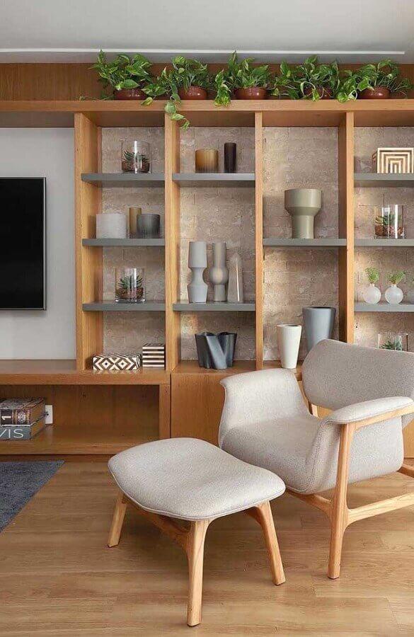 poltrona decorativa com puff para sala decorada com estante de madeira Foto Pinterest
