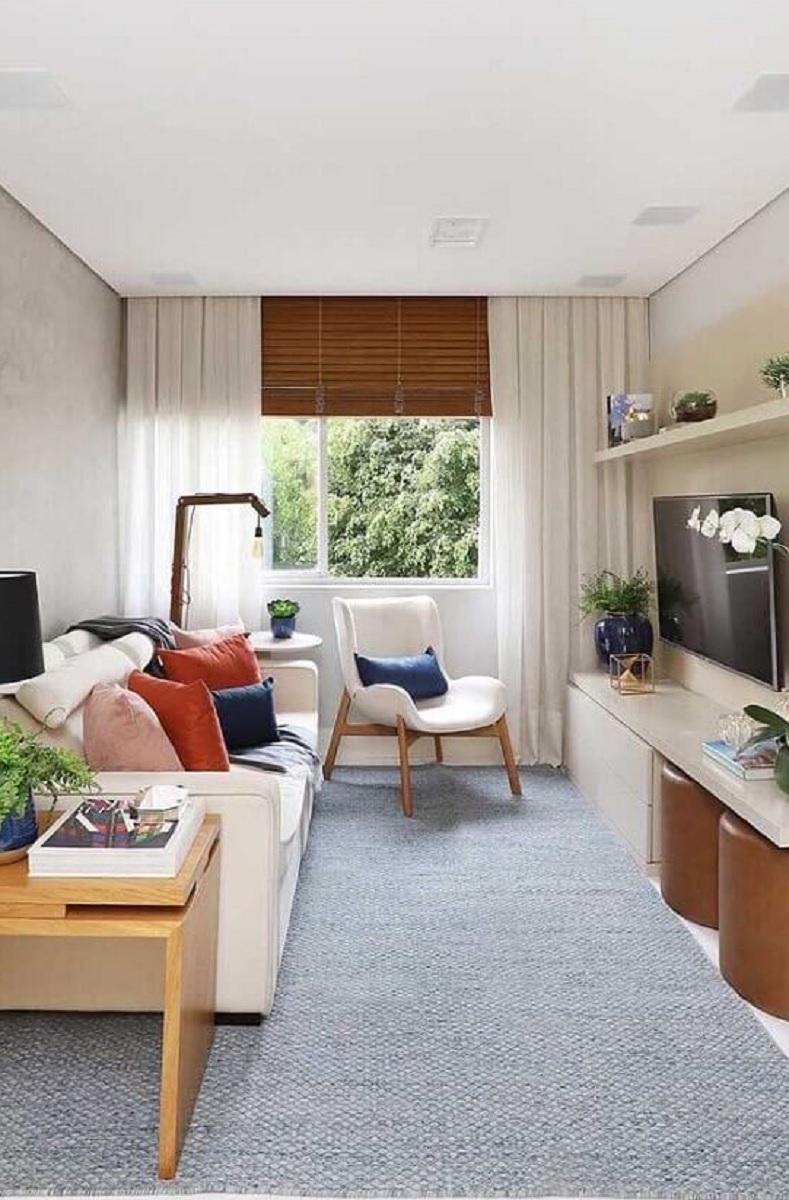 poltrona para sala de estar pequena decorada com almofadas coloridas e tapete cinza Foto Pinterest