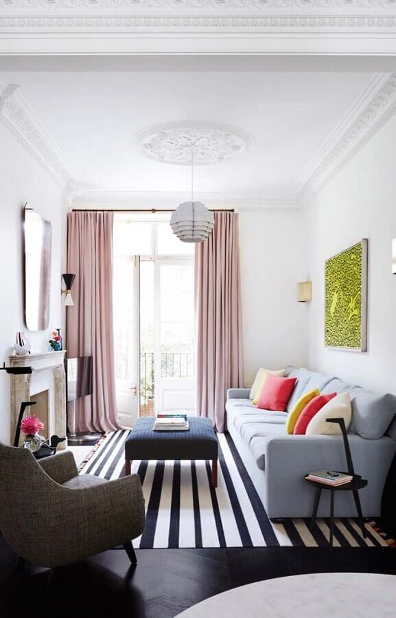 poltrona para sala pequena decorada com cortina rosa e tapete listrado preto e branco Foto Apartment Therapy