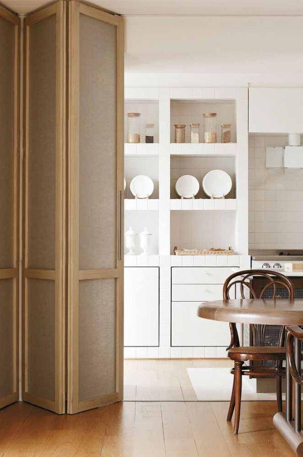 Porta sanfonada na cozinha com armários brancos