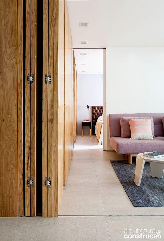 Sala de estar com porta sanfonada de madeira