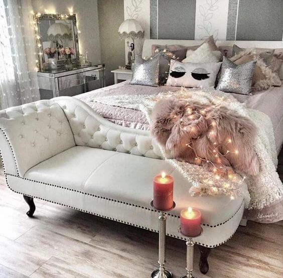 Divã cinza na ponta da cama moderna
