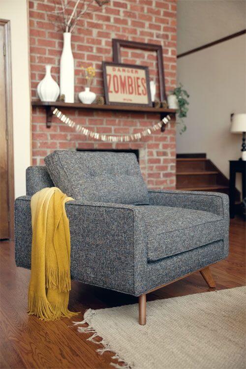 Sala com poltrona cinza e papel de parede de tijolinho