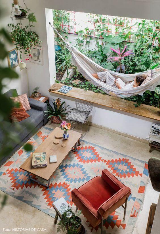 Tapete para sala boho chic com rede confortável e sofá cinza