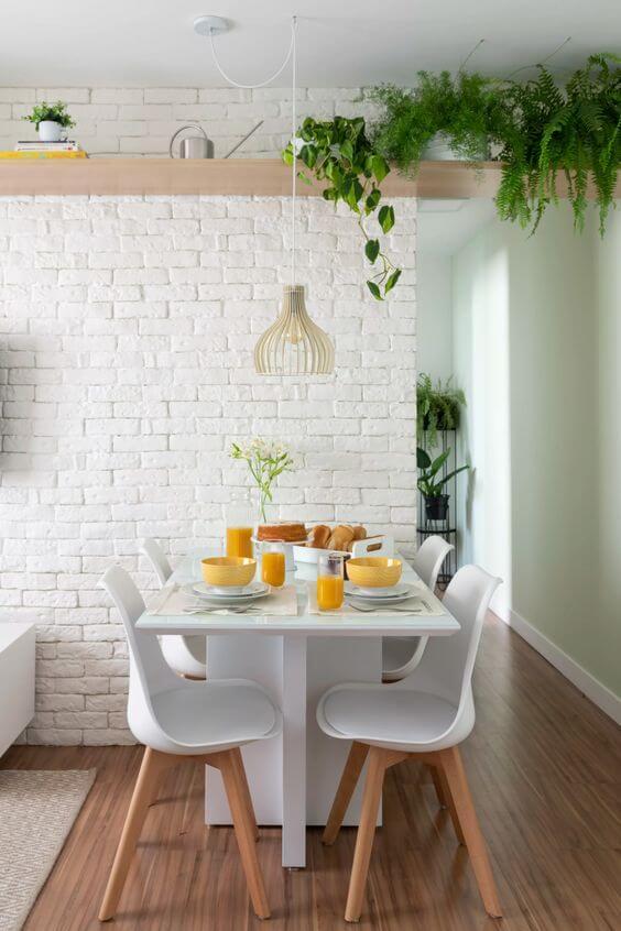 Sala de jantar branca com papel de parede tijolinho