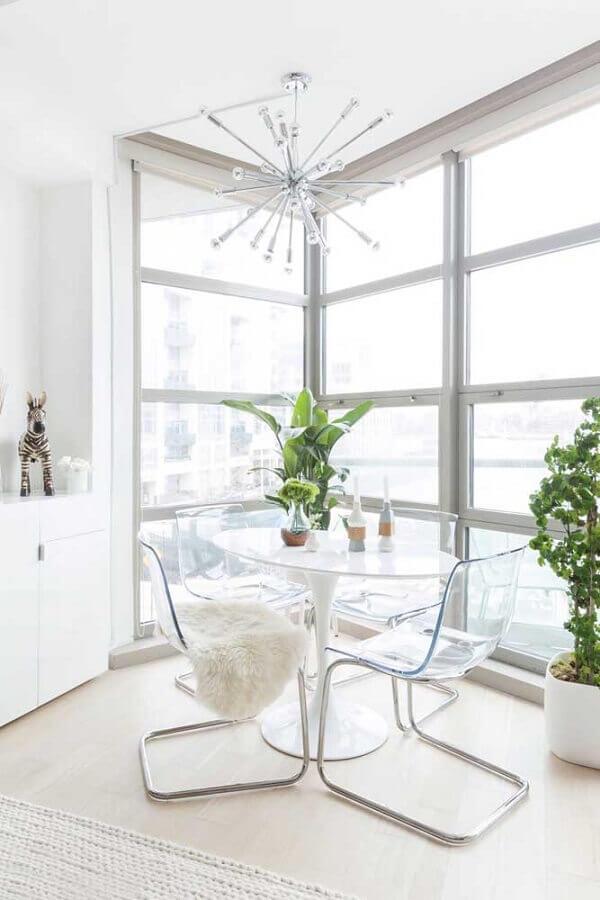 sala de jantar branca decorada com mesa de vidro e cadeira transparente Foto Otimizi