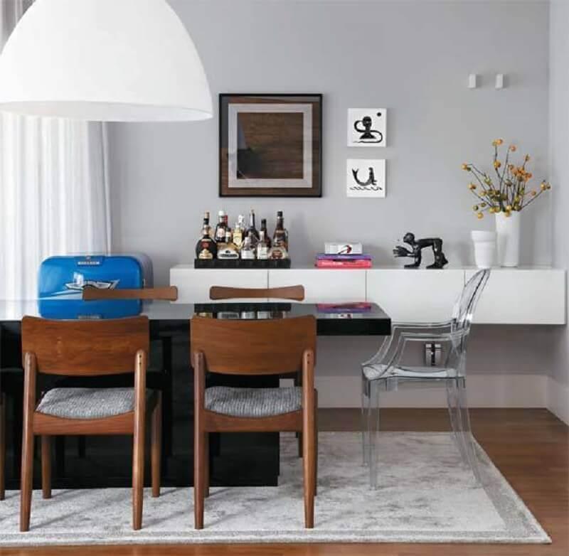 sala de jantar moderna decorada com mesa com cadeiras transparentes e cadeiras de madeira Foto Mariah Lopes