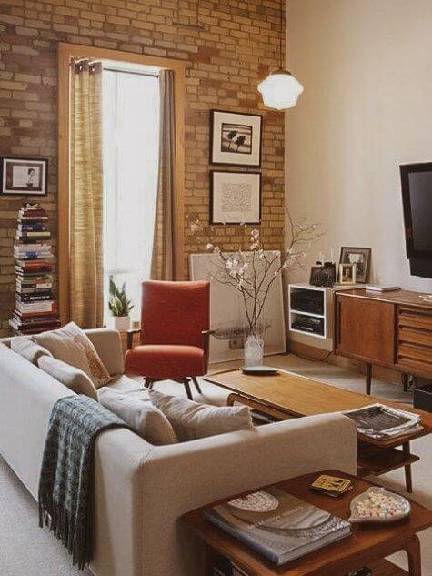 Sala de estar com tijolinho a vista e decoração neutra com rack de madeira
