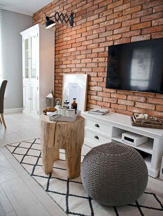 Sala de estar com tijolinho a vista na parede da rack
