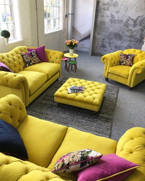 Sofá chesterfield amarelo com almofada roxa