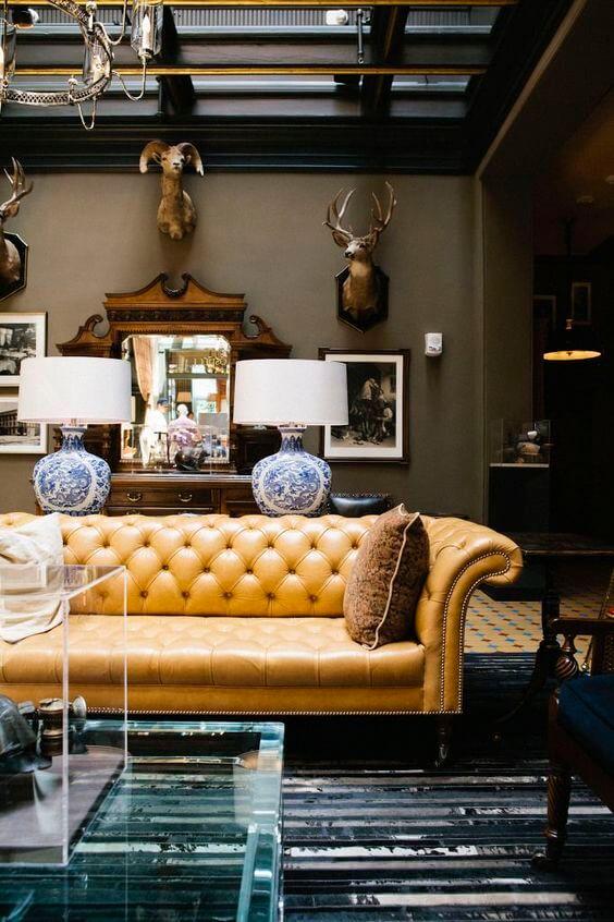 Sofá chesterfield amarelo na sala clássica