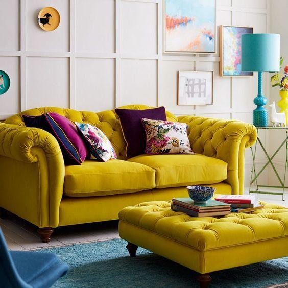 Sofá amarelo com almofadas roxas
