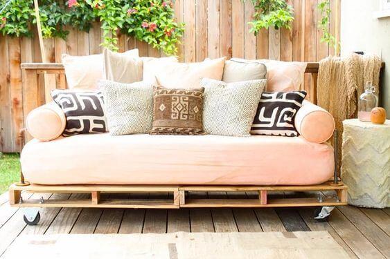Sofá de pallet rosa com almofadas estampadas