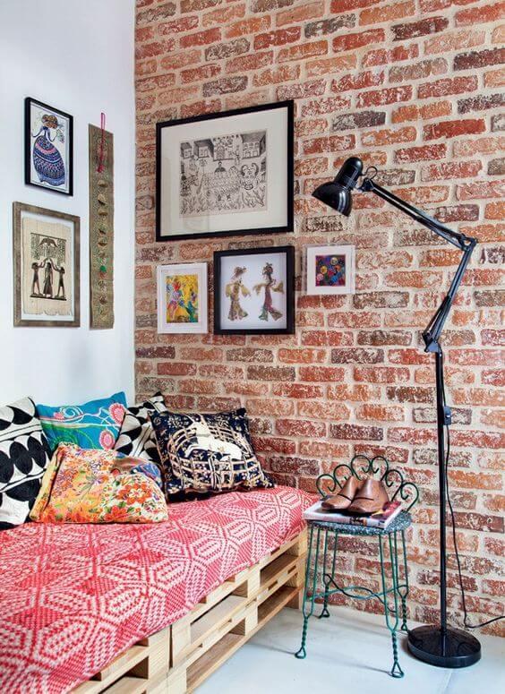 Decoração de sala de estar industrial com parede de tijolinho a vista e sofa de pallet