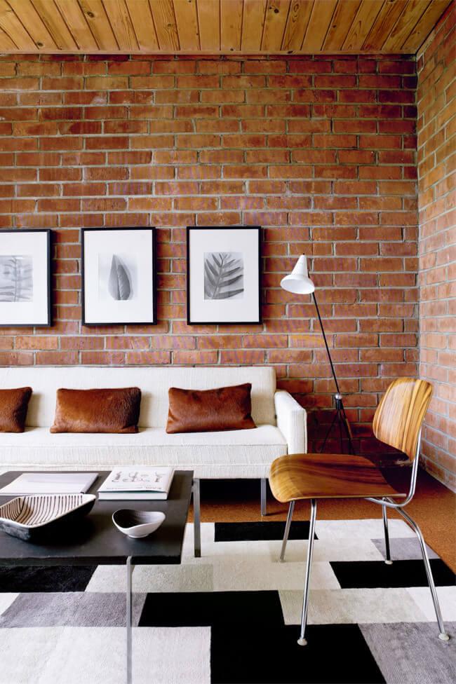 Sala com tijolinho a vista e móveis de madeira neutros