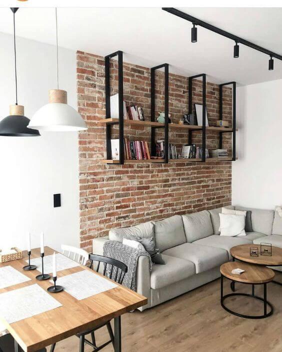 Sala com parede de tijolinho e sofa cinza moderno