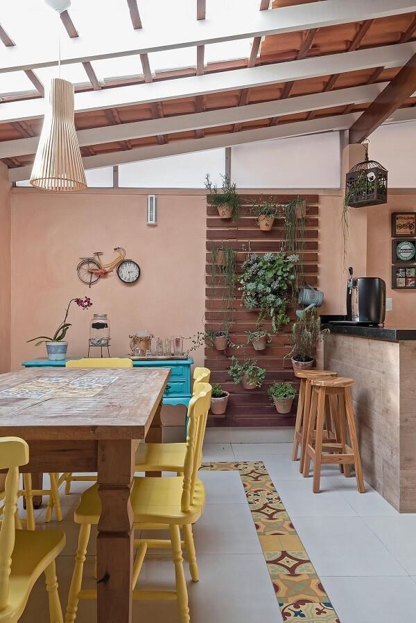 Área gourmet rústica com cadeiras de madeira amarela e piso com ladrilho