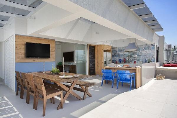 Área gourmet rústica com mesa e bancada com cadeiras