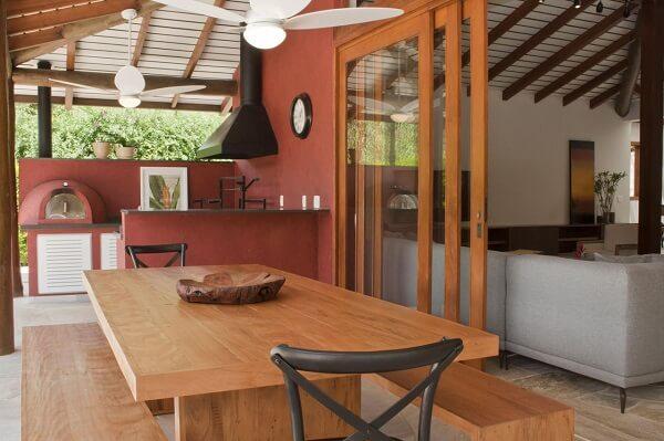 Área gourmet rústica com parede vermelha e mesa de madeira
