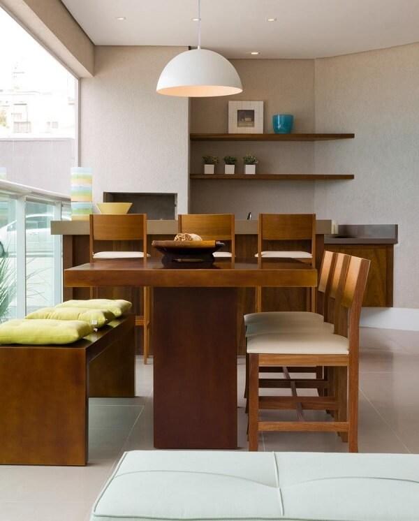 Área gourmet rústica pequena com mesa de madeira