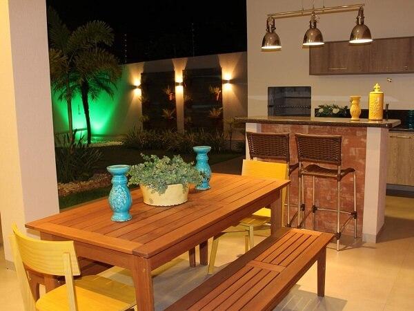 Área gourmet rústica simples com mesa e banco de madeira