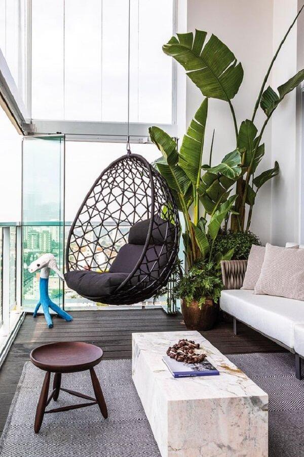 A cadeira de corda náutica com estrutura de balanço complementa a decoração da varanda.